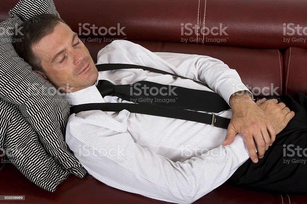 businessman sleeping on couch stock photo