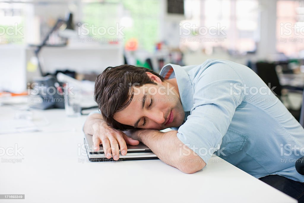 Businessman sleeping on laptop at desk in office stock photo