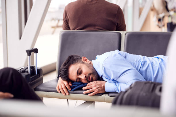 businessman sleeping on seats in airport departure lounge because of delay - stranded stock pictures, royalty-free photos & images
