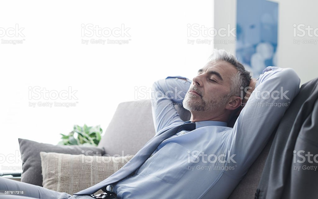 Businessman sleeping on the couch stock photo