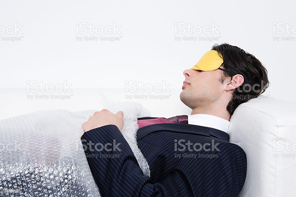 Businessman sleeping under bubble wrap 免版稅 stock photo