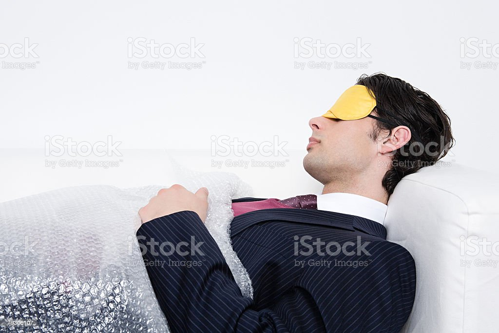 Businessman sleeping under bubble wrap stock photo