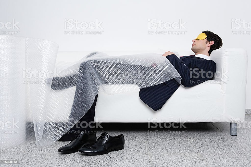 Businessman sleeping under bubble wrap royalty-free stock photo
