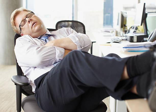 homme d'affaires de couchage-vous au bureau pour travailler avec - faire un somme photos et images de collection