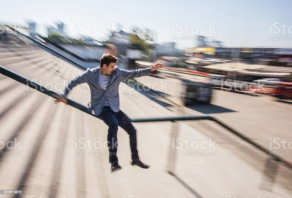 Businessman sliding down the rail in blurred motion. stock photo