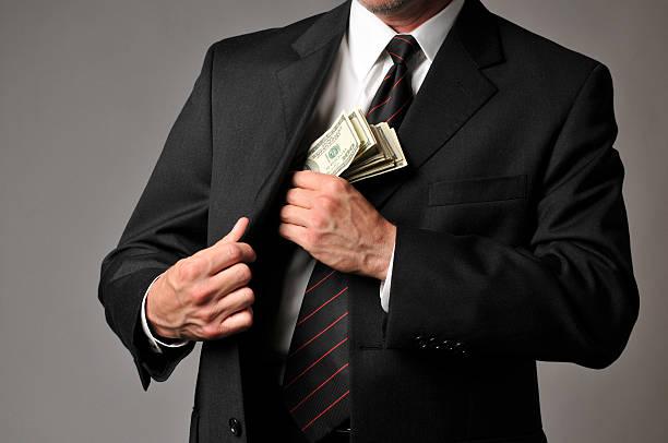 empresário vestindo uma pilha de dinheiro para o seu fato de bolso - corruption imagens e fotografias de stock