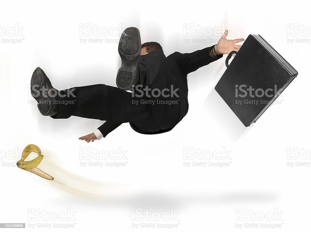A businessman slipping on a banana peel stock photo