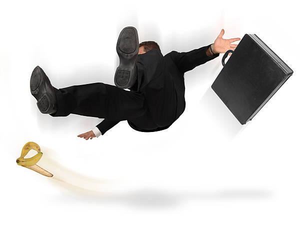 A businessman slipping on a banana peel Businessman slipping and falling from a banana peel on a white background banana peel stock pictures, royalty-free photos & images