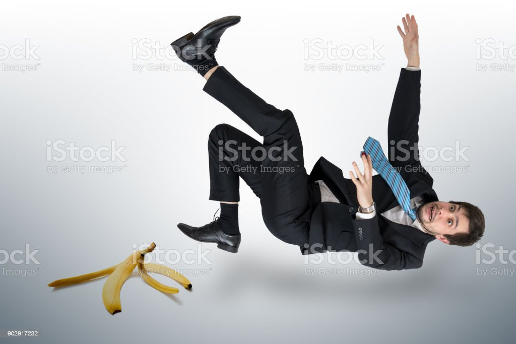 Businessman slipping on a banana peel. stock photo