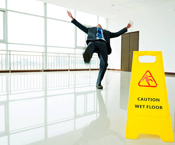 Businessman slipping on wet floor Businessman slipping on wet floor with warning sign slippery. slippery stock pictures, royalty-free photos & images