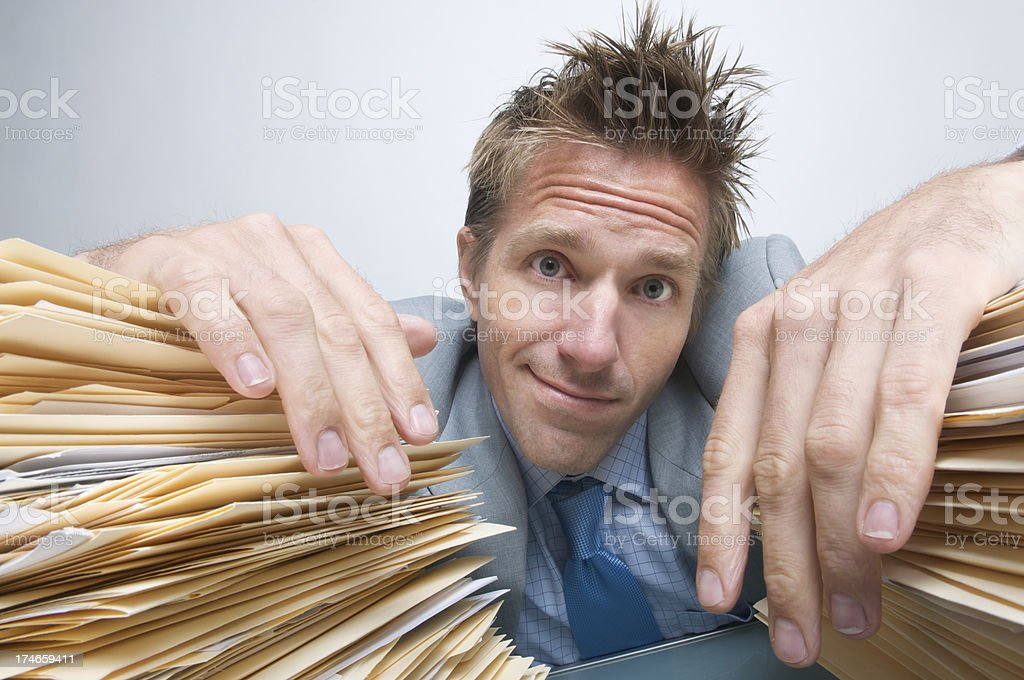 Businessman Smiles from between Stacks of Paperwork royalty-free stock photo