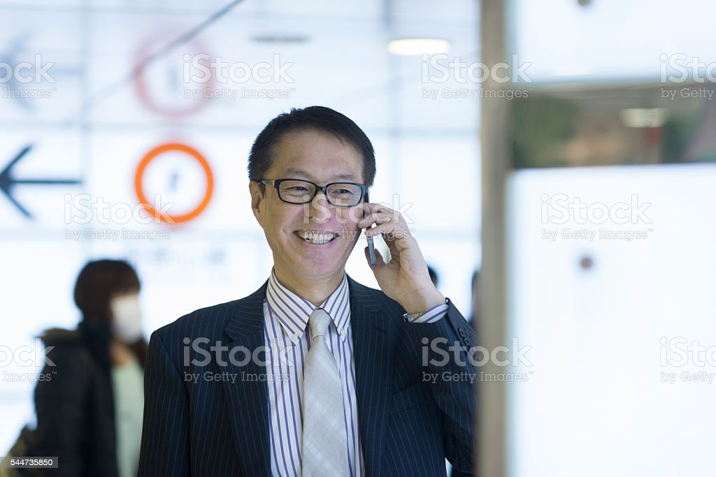 Businessman smiling and talking on mobile phone. – Foto