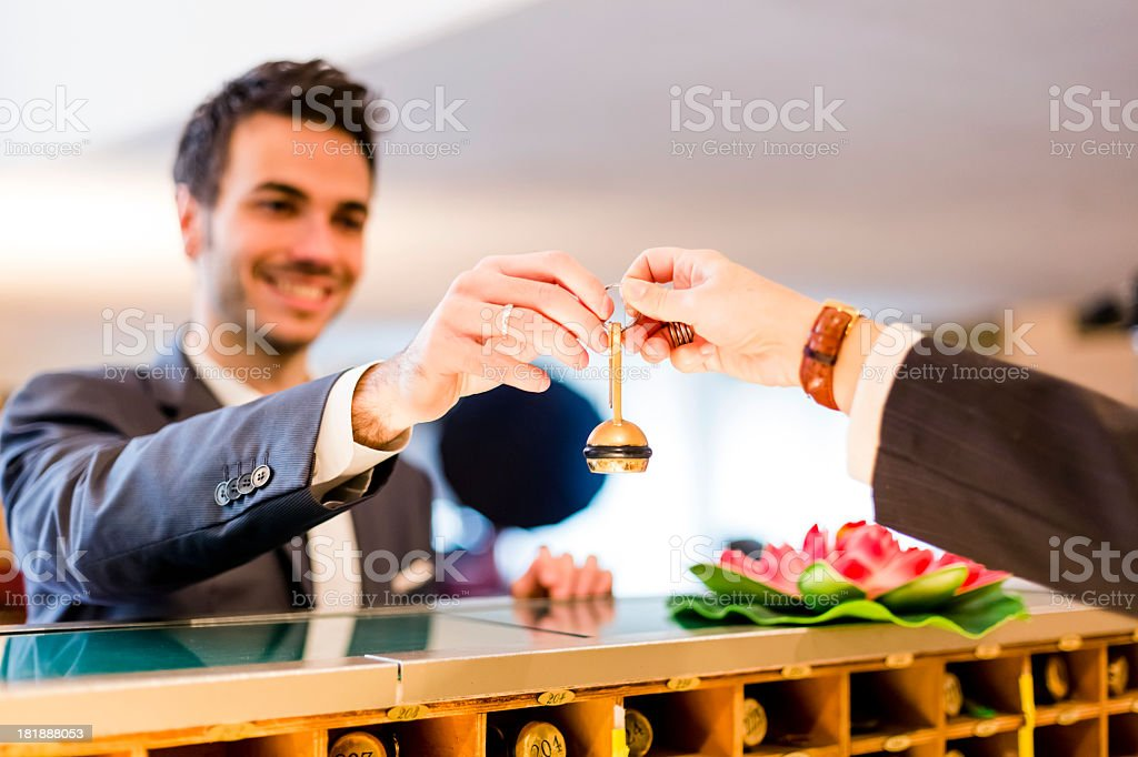 Businessman smiling as he checks in and receives hotel key stock photo