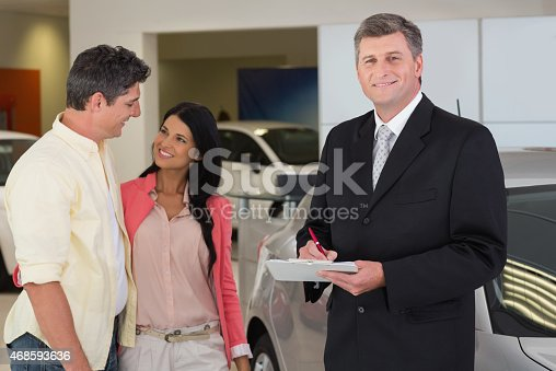 1138561232 istock photo Businessman smiling at camera while writing on clipboard 468593636