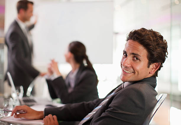 Businessman smiling at desk stock photo