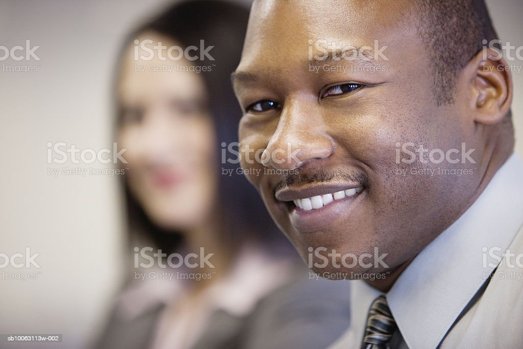 Businessman smiling, businesswoman in background foto royalty-free