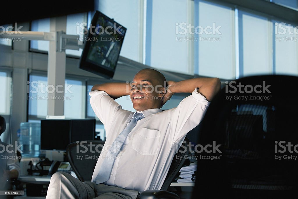 Businessman smiling while relaxing in office royalty-free stock photo