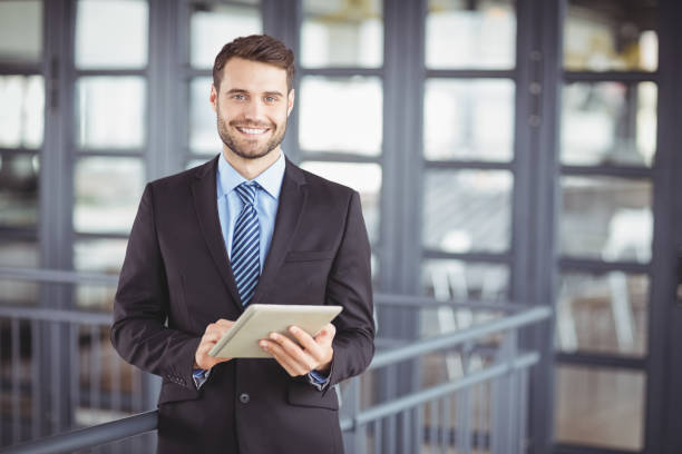 Businessman smiling while using digital tablet stock photo