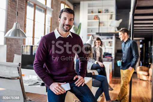 Businessman smiling with mobile phone sitting on his desk, colleagues working in the background.