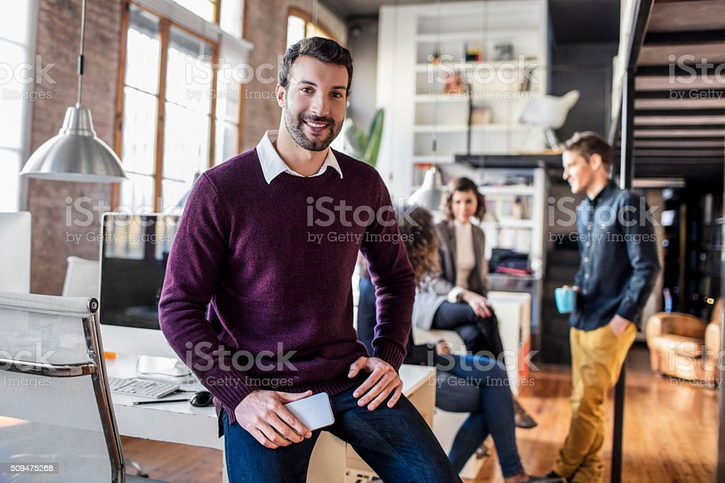 Businessman smiling with mobile phone sitting on his desk stock photo