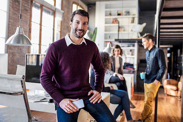 businessman smiling with mobile phone sitting on his desk - 20 29 years stock photos and pictures