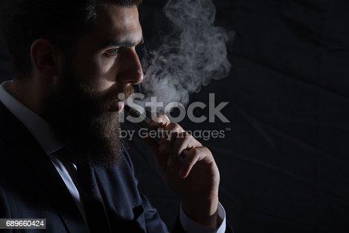 istock Businessman smokes electronic cigarette 689660424