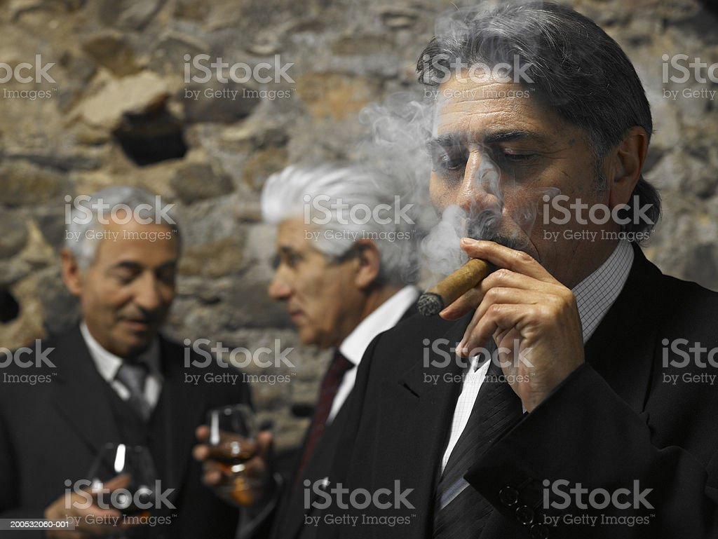 Businessman smoking cigar in restaurant, businessmen in background royalty-free stock photo