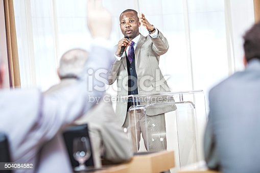 1180973515 istock photo businessman speaking at a business conference 504084582