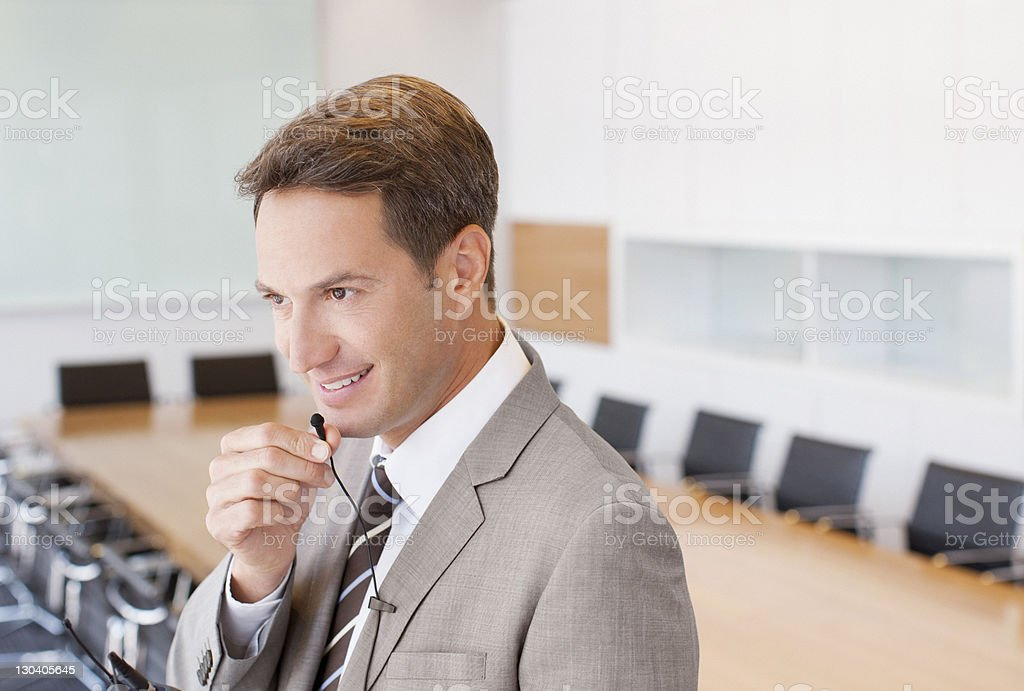 Businessman speaking into microphone in conference room stock photo