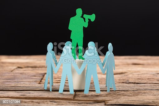 Green paper businessman speaking through megaphone surrounded by team on wooden table against black background