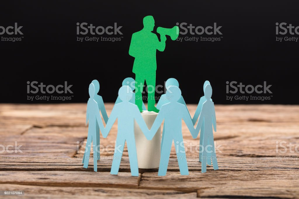 Businessman Speaking Through Megaphone Surrounded By Team stock photo