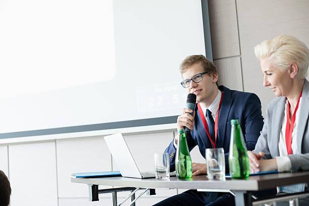 businessman speaking through microphone while sitting - leitungswasser trinken stock-fotos und bilder