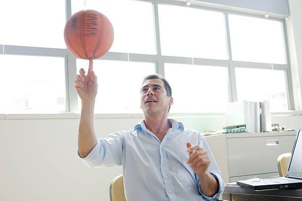 Geschäftsmann spinning einen basketball auf finger im Büro – Foto