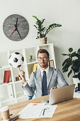 happy businessman spinning soccer ball on finger at workplace