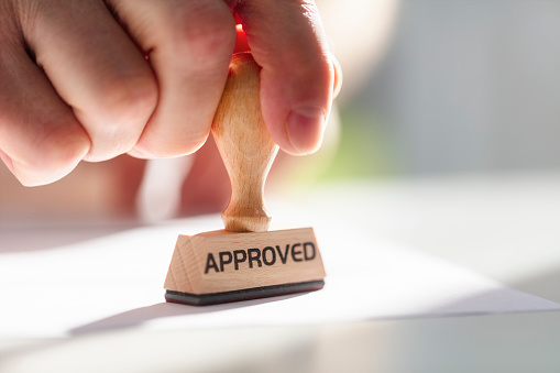 Businessman or notary public stamping approved stamp on document in meeting