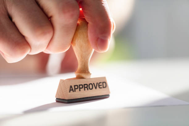 Businessman stamping approved stamp on document in meeting stock photo