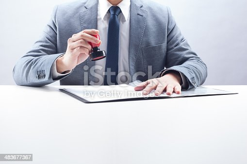 Businessman stamping the document at the desk.