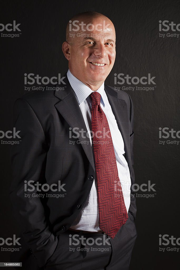 Businessman standing against black background royalty-free stock photo