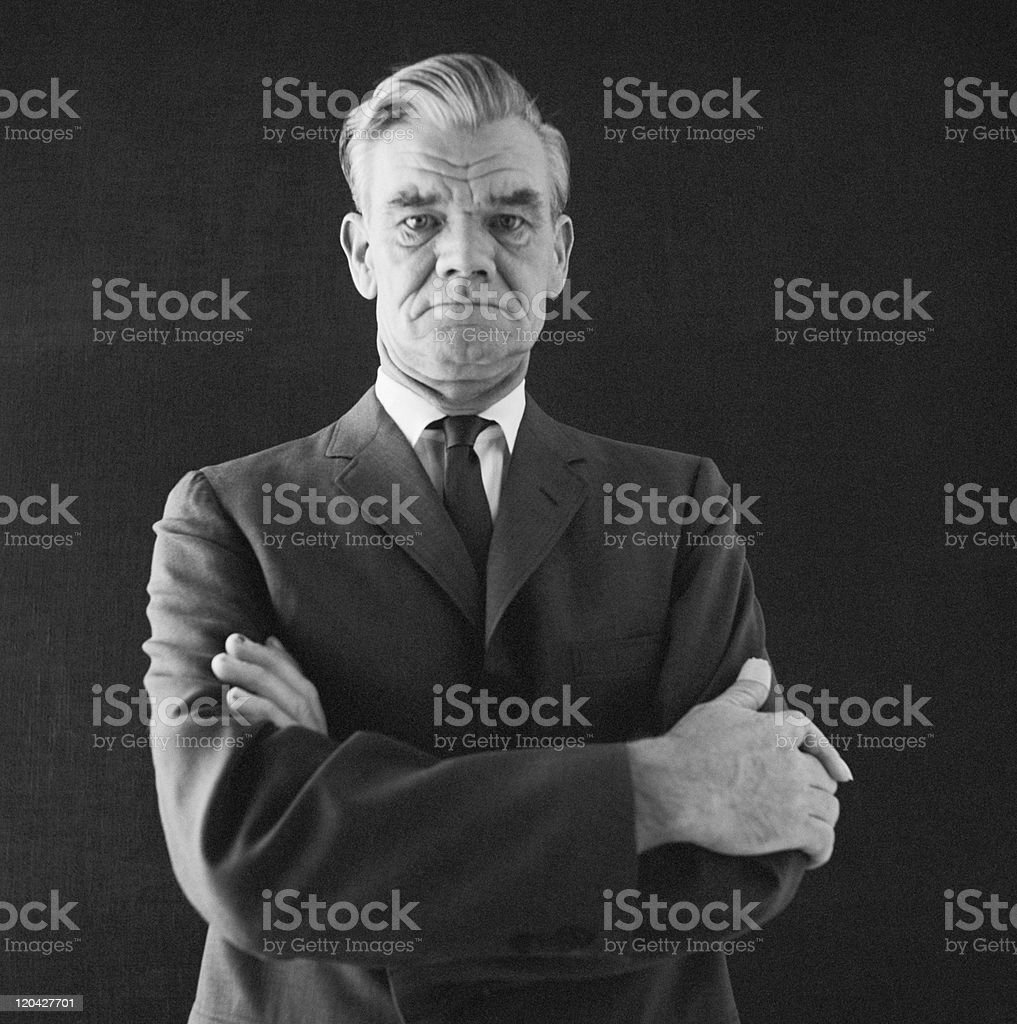 Businessman standing against black background, portrait stock photo