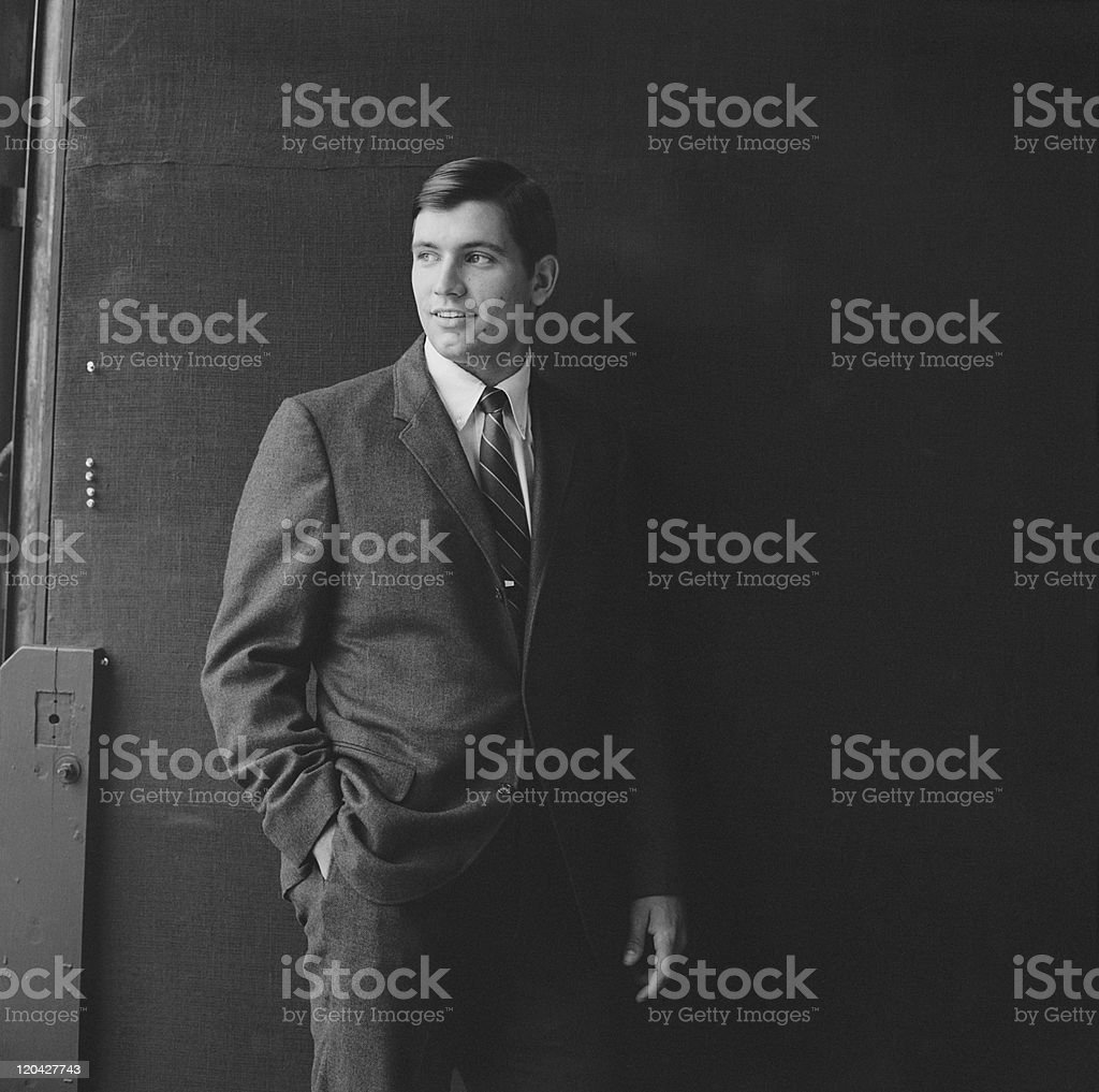 Businessman standing against black background, smiling stock photo