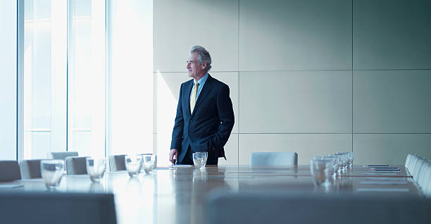 Businessman standing alone in conference room stock photo