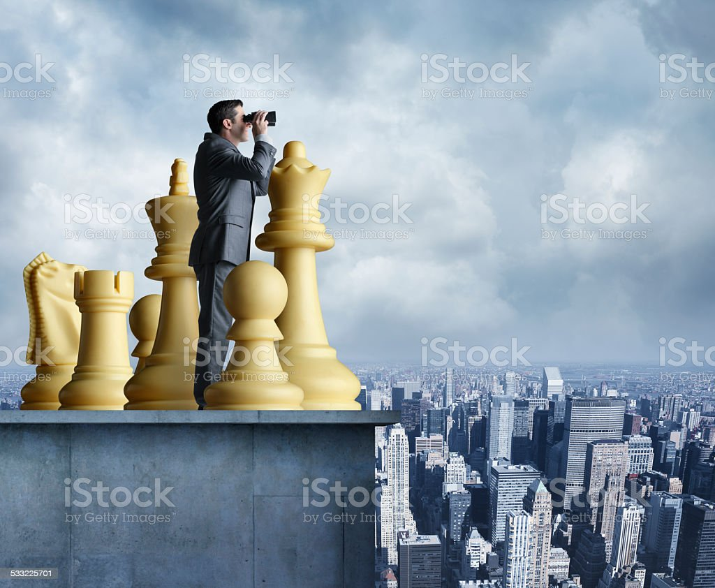 Businessman standing among chess pieces looks through binoculars stock photo