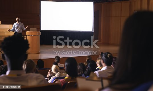 1133973551 istock photo Businessman standing and giving presentation in auditorium 1133856103