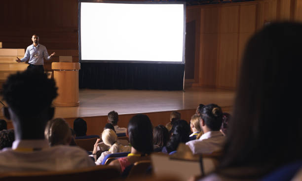 Businessman standing and giving presentation in auditorium Rear view of mixed race audience listening to the presentation while mixed race businessman giving presentation in auditorium overhead projector stock pictures, royalty-free photos & images