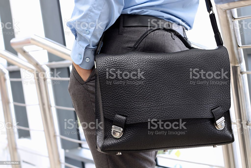 Businessman standing  and holding  a  leather briefcase on his s stock photo