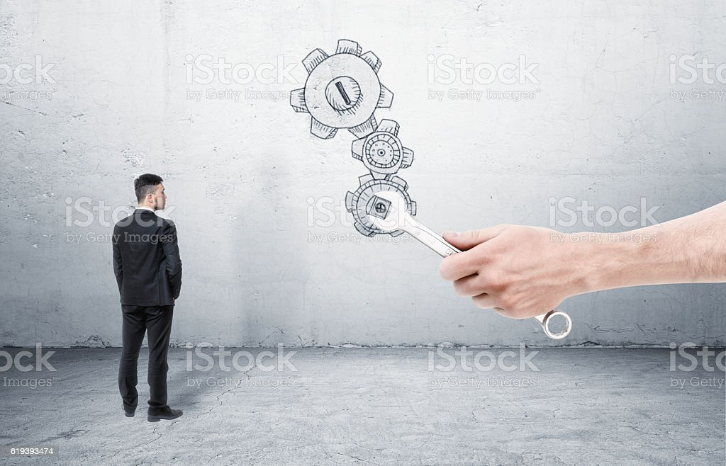 Businessman standing and looking at big hand with wrench, which stock photo