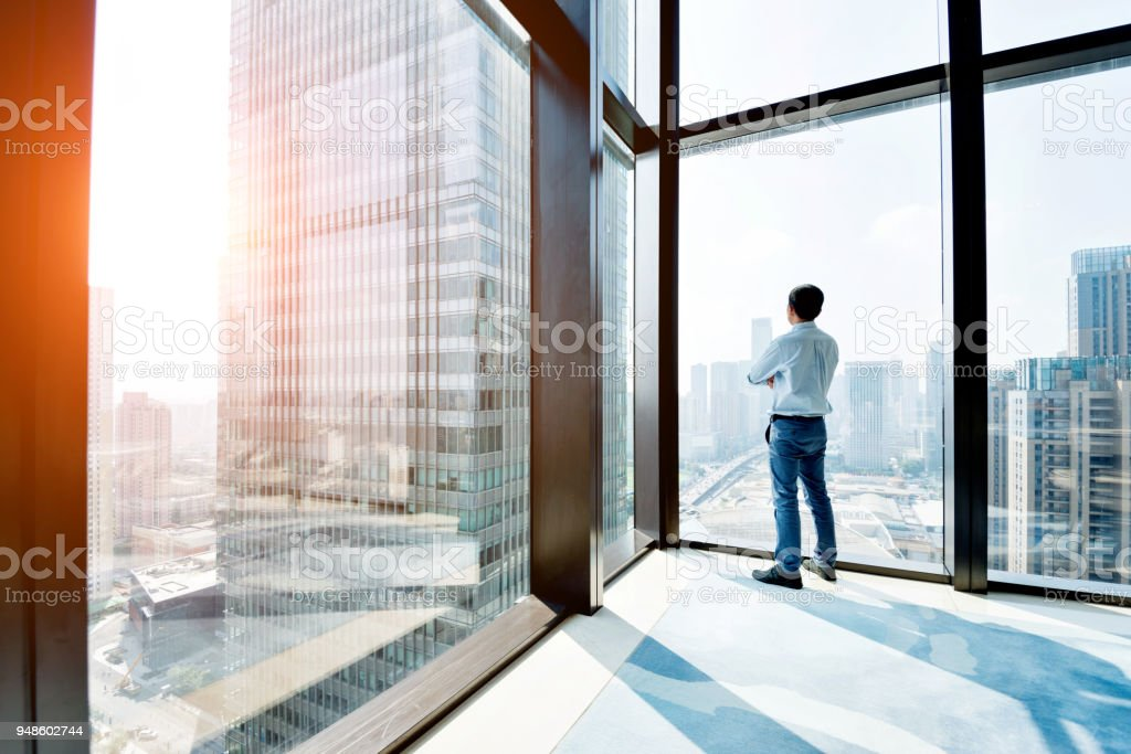 Businessman standing and looking at cityscape stock photo