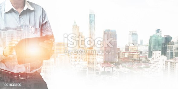 istock Businessman  standing and operate tablet to control and connect big data of real estate background. 1001933100