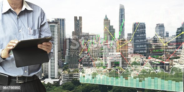 istock Businessman  standing and operate tablet to control and connect big data of real estate sector stock market index with chart and graph background. 984766950