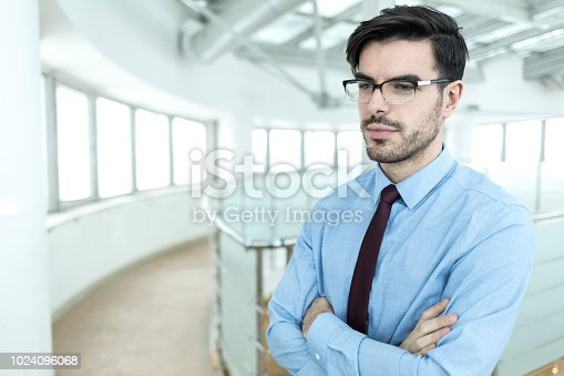 825082848istockphoto Businessman standing arms crossed in office 1024096068